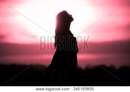 Youth Woman Soul At Red Sun Meditation Awaiting Future Times. Silhouette In Front Of Sunset Or Sunri