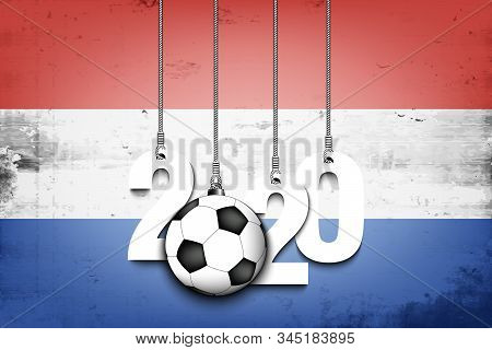 Figures 2020 And Soccer Ball Hanging On Strings Against The Background Of The Flag Of Netherlands. D
