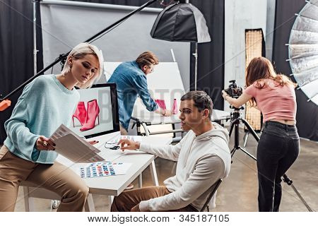 Attractive Art Director Looking At Photos Near Computer Monitor And Assistant