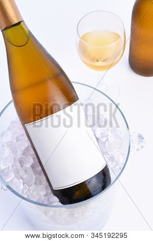 Closeup of a White Wine bottle with blank label in an crystal ice bucket with a glass and bottle in the background .