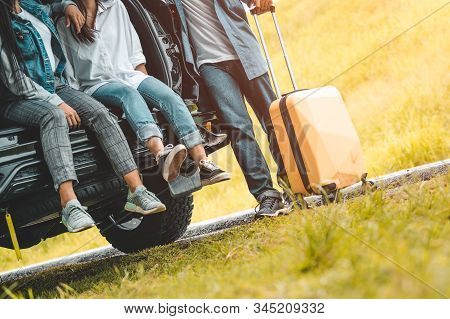 Closeup Lower Body Of Group Of Friends Relaxing On Suv Car Trunk With Trolly Luggage Along Road Trip