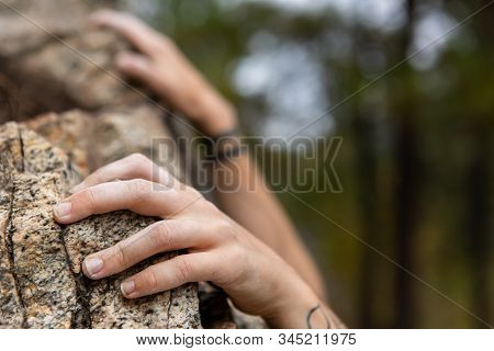 Hanging On A Rock By Fingertips As A Caucasian Person Attempts To Grip Rugged Crag. Selective Focus