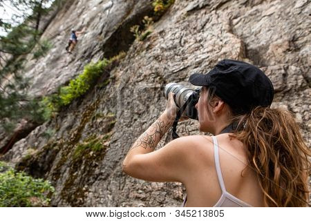A Low Angle View As A Woman Uses A Professional Camera With Large Lens To Photograph A Man Climbing