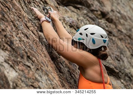 A Close Up And Side View Of A Female Rock Climber Ascending A Difficult Stone Crag, Wearing Safety H