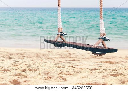 Wooden Swings On The Sand Beach And Sea Of Tropical Island