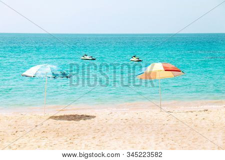 Two Colourful Beach Umbrella On The Beach With Two Jet Ski In Sea And No People In There.
