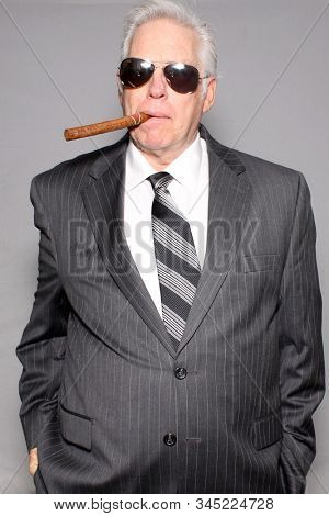 Business man with a Cigar. A business man in a pin striped suit holds and enjoys a fine cigar. On a grey background. Room for text overlay. People world wide enjoy fine cigars and tobacco products.