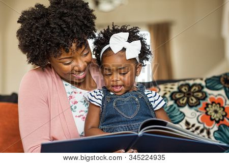 Mother Reading A Book To Her Little Girl.