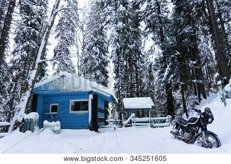View At Wooden Buiding Toned In Classic Blue In Winter Forest, Motorcycle Is On A Side, Snow Is All