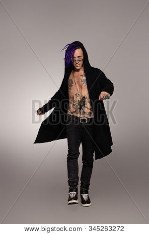 Full length portrait of a punk rock musician posing at studio. Youth alternative culture.