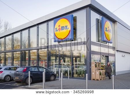 Buckingham, Uk - December 04, 2019. Lidl Supermarket Store Exterior, With Woman Shopper Outside The