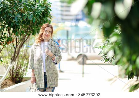A Woman 30-35 Years Old Walks In The Early Autumn In The European Park While On Vacation.