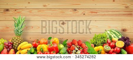 Fresh fruits and vegetables on wooden wall background from boards.