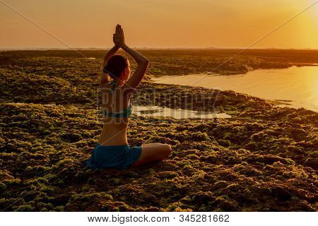 Young Woman Meditating, Practicing Yoga And Pranayama At The Beach. Sunset Yoga Practice. Sun Reflec