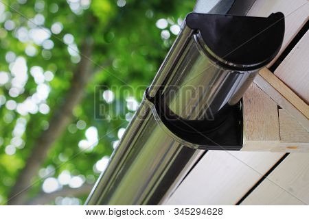 Rain Gutter Pipeline System Installation. Roofing Construction. Rain Gutter System And Roof Protecti
