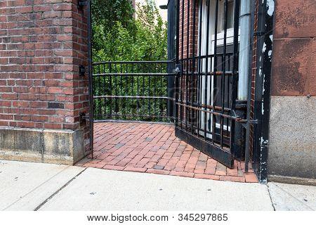 Brick Passageway Between Buildings With Partially Open Gate Door, Horizontal Aspect