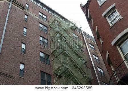 Old Residential Apartment Building With Metal Fire Escape Caged In Chain Link, Horizontal Aspect