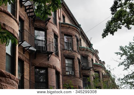 View Looking Down A Row Of Old Brownstone Apartment Buildings With Half Round Fronts, Metal Baconies