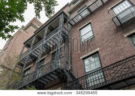 Elaborate Balcony Railings On The Face Of Old Brick Apartment Buildings, View Looking Up, Horizontal