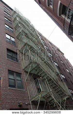 Extreme Upward View Of Caged Fire Escape In An Alley Between Two Urban Housing Units, Vertical Aspec