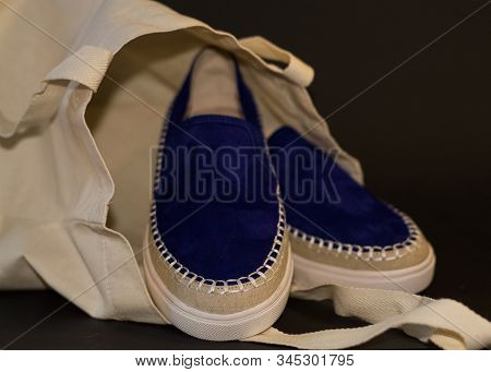 On Black Background Of The Shopping Bag, Shopper, Of Beige Cloth And Blue Slipons Of Suede. Street F