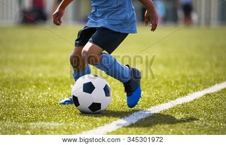 African American Young Boy Playing Soccer In A Stadium Pitch. Child Running With Soccer Ball Along T