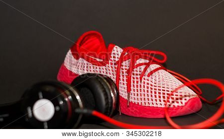On Black Background, Red Sneakers With Large Black Headphones To Listen To Music When Running. Sport