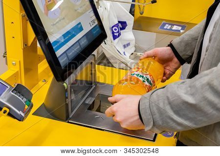 Moscow, Russia - January 7, 2020: A Man Verifies A Bottle Of Mirinda Orange Water At A Self-service