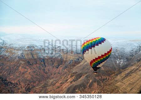 Colorful Hot Air Balloon Flying Over The Famous Tourist Place Cappadociaat At Winter Time