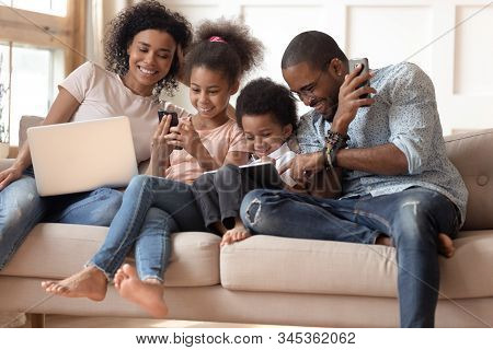 Happy Addicted To Gadgets Black Family Using Different Devices.