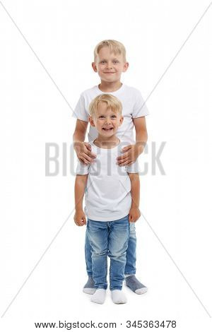 Friendly family. Older brother is hugging younger boy, standing isolated on a white background. Happy siblings. Two little brothers. Concept of people and family,