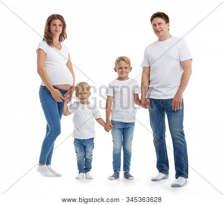 Happy parents: pregnant mother and father with lovely two sons are stand holding hands and smiling, isolated on a white background. Happy friendly family. Concept of people and family