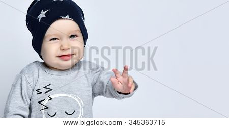 Little Baby Boy Toddler In Grey Casual Jumpsuit, Black Cap With Stars , Smiling And Gesticulating Ov