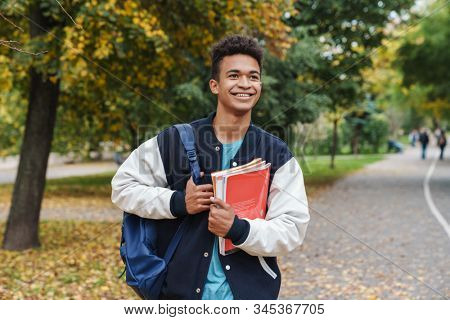 Cheerful african boy teenager walking at the park, carrying backpack and textbooks