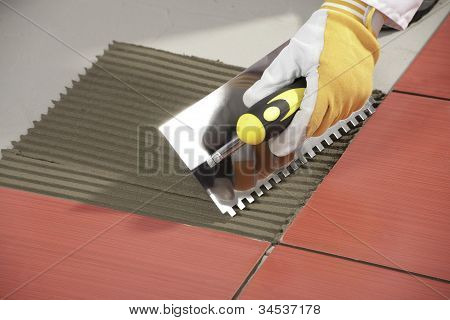 Worker With Notched Trowel Install Red Tiles With Tile Adhesive