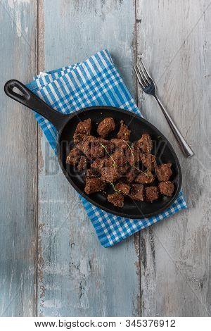 Fried Liver Cubes In Black Griddle On Wooden Background