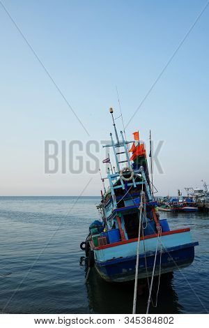 A fishing boat held by ropes facing towards vastness of sky and sea. Shot from behind. poster