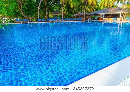Crystal Clear Pool By The Tropical Sea, Secluded Island For Relaxation. Palm Trees Are Reflected In
