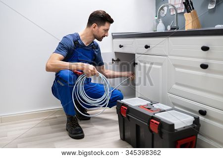 Male Plumber Cleaning Clogged Sink Pipe In Kitchen