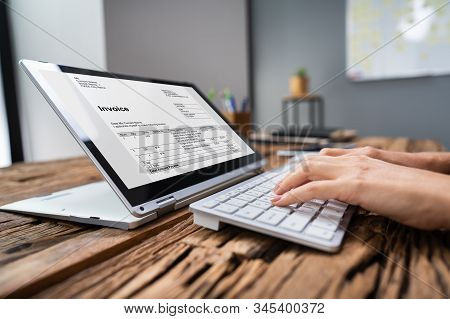 Businessperson Analyzing Invoice On Laptop