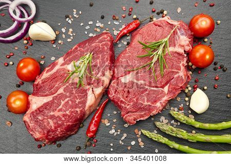 Raw Rib Eye Steak With Spices And Vegetables. Ingredients For Restaurant Meal. Fresh Meat, Salt, Ros