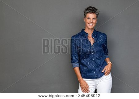 Happy mature businesswoman standing on grey background. Successful senior business woman with hand in pocket looking at camera. Portrait of confident and reliable lady standing against gray wall.
