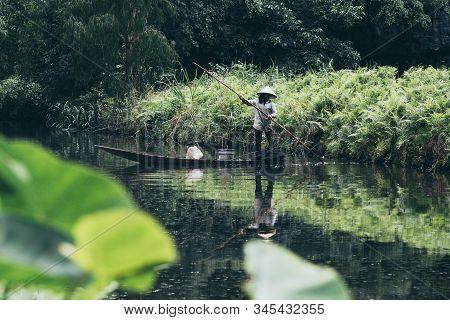 Ning Binh, Vietnam - May 2019: Vietnamese Woman In A Wooden Rowing Boat Fishing In Trang An Nature P