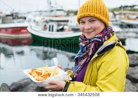 Young Woman In Yellow Raincoat Holds A Portion Of Fish And Chips In Husavik, Iceland