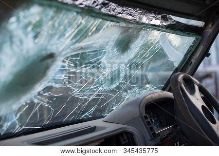 Bullet Hole On A Car Windshield. Car Window After A Raid Has A Bullet Hole. Broken Glass. Bullet Hol