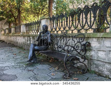 Kutaisi, Georgia, October 13, 2019 : Bronze Sculpture Of Boris Gaponov Sitting On A Bench With A Boo
