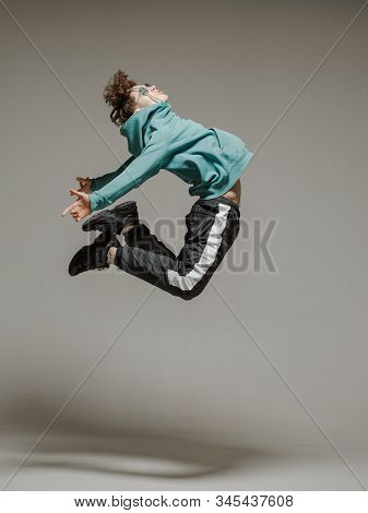 Guy Dancing Contemporary Dance In Studio. Neutral Grey Background. Acrobatic Bboy Dancer.