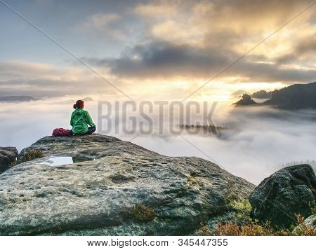 Back Silhouette Of Hiker Woman Admiring Amazing Landscape Over Misty Mountains In Sunset Time.