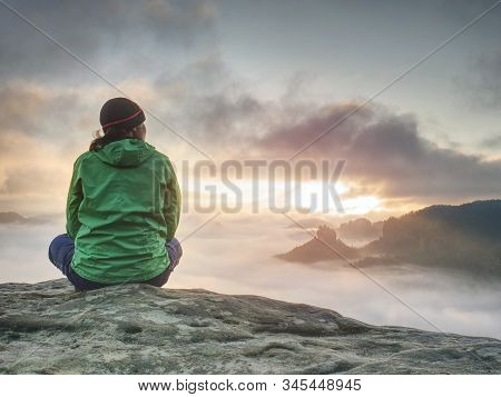 Alone Travel Woman Hiker Sits On The Edge Of The Cliff And Enjoying Sunrise Looking At The Valley An