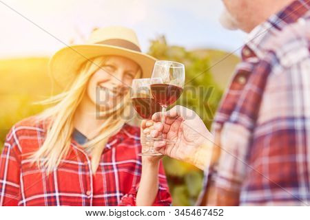 Happy couple with glass of red wine having wine tasting and tasting in vineyard